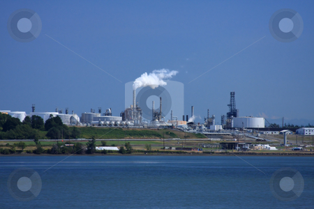 Oil Refinery View stock photo, Oil refinery billowing smoke into blue sky by Steve Stedman