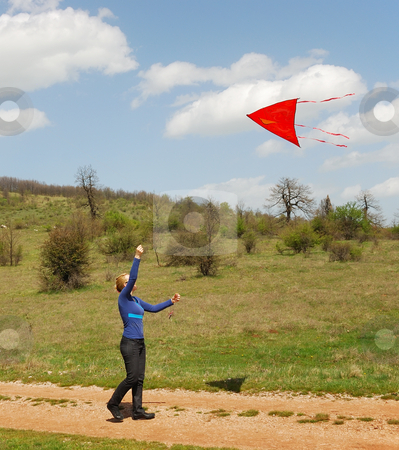 Woman and a kite stock photo, A woman is playing with a kite by Ivan Paunovic