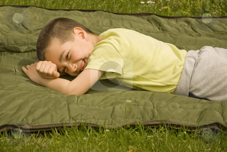Joy stock photo, A boy is lying on a blanket and enjoying the sun by Ivan Paunovic