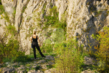 Girl on a cliff stock photo, A girl is standing on a cliff by Ivan Paunovic