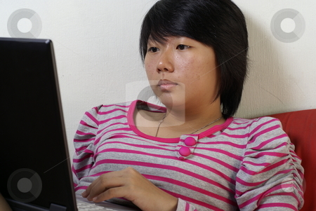 Woman on laptop stock photo, Young asian lady on laptop. by Wong Chee Yen