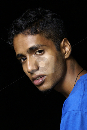 Young indian man portrait stock photo, Young indian man portrait wearing blue with black background by Wong Chee Yen