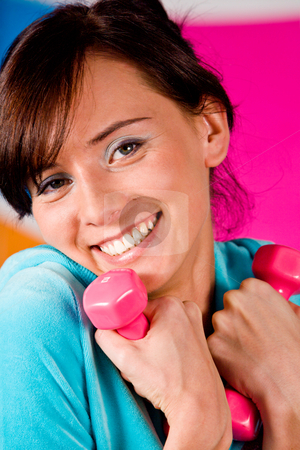 I Like Fitness stock photo, Beautiful young woman curls dumbbells with a happy smile. by Vitaly Sokolovskiy