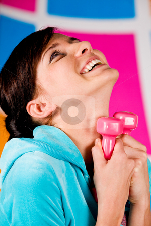 I Like Fitness stock photo, Beautiful young woman curls dumbbells with a happy smile by Vitaly Sokolovskiy