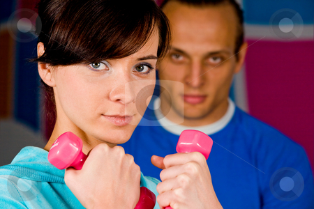 Workout with personal trainer stock photo, Woman at the health club with her personal trainer by Vitaly Sokolovskiy