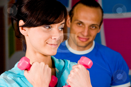 Workout with personal trainer stock photo, Smiling young woman at the health club with her personal trainer by Vitaly Sokolovskiy