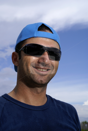 Caucasian man smiling outdoors stock photo, Caucasian man smiling outdoors with sunglasses and blue cap by Wong Chee Yen