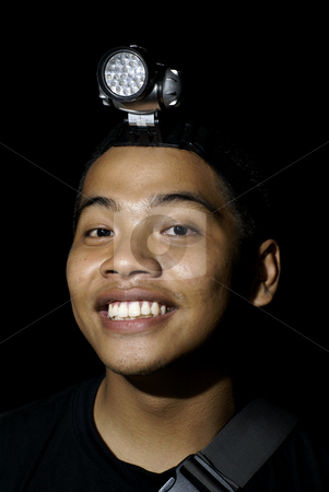 Man wearing headlamp stock photo, Young asian man with LED head lamp by Wong Chee Yen