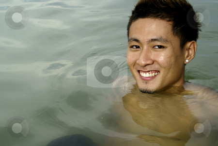 Smiling asian man in sea water stock photo, Smiling asian man in sea water by Wong Chee Yen