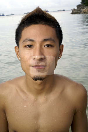 Chinese asian man at beach stock photo, Chinese asian man at beach with earrings by Wong Chee Yen