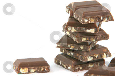Closeup chocolate pieces stock photo, Closeup chocolate pieces on stack with copy space isolated on white background food and sweets concepts by EVANGELOS THOMAIDIS