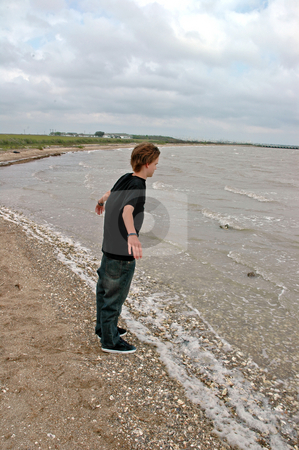 Teen at the Shoreline stock photo, A teen leans into the wind at the shoreline of the sea by Jeff Clow