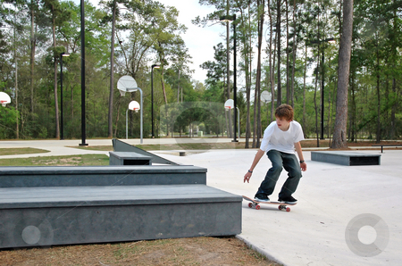 Teen Skater at the Park stock photo, A teen skater gets ready to do a trick at a suburban park by Jeff Clow