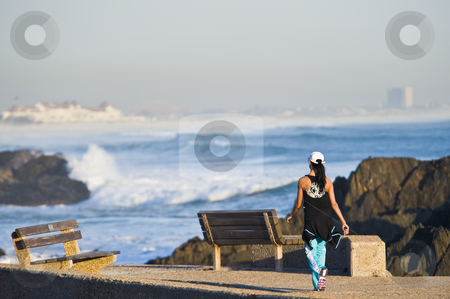 Fit young lady walking next to beach stock photo, A fit young lady walking and jogging next to the beach in the late afternoon. by Nicolaas Traut