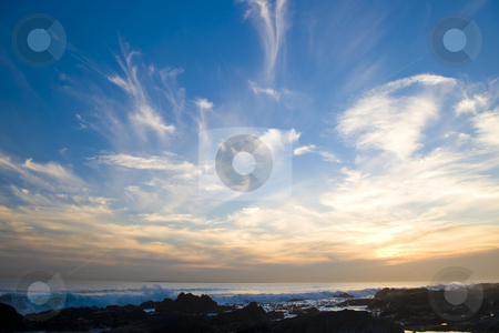 Sunset over the sea stock photo, Vivid sunset over the sea with deep blue skies and bright sun spots. by Nicolaas Traut