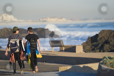 Two boys walking next to the beach with body-boards stock photo, Two boys with body-boards wearing wetsuits and carrying fins, walking next to the beach. by Nicolaas Traut