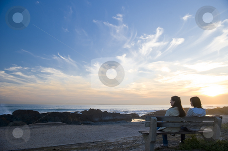 Sunset over the sea stock photo, Vivid sunset over the sea with deep blue skies and bright sun spots.  People are sitting on a bench overlooking the sea. by Nicolaas Traut