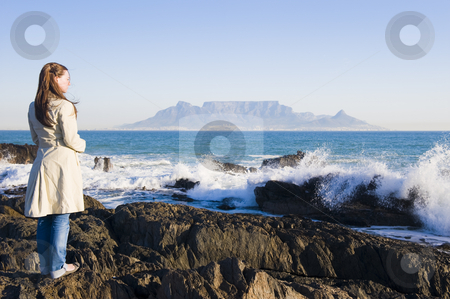 Table mountain Cape Town stock photo, Table Mountain - the world famous landmark in Cape Town, South Africa. Picture taken on a clear Winters day from the Blouberg Strand beach. A girl is standing on some rocks in the foreground, wearing a Winter coat. by Nicolaas Traut