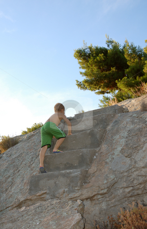 Boy on a stairway stock photo, A boy is climbing on a stairway on a rock by Ivan Paunovic
