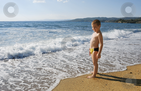 Boy on a beach stock photo, A boy is standing on a beach looking at sea wave by Ivan Paunovic