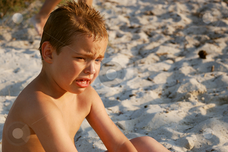 Boy crying stock photo, A boy is crying sitting in a sand by Ivan Paunovic