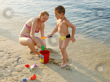 Playing stock photo, A mother and a son playing in the sand on a beach by Ivan Paunovic