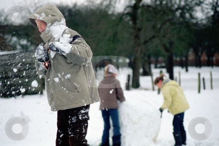 Snowball fight stock photo, Boy having snow thrown at him by Mpixis World