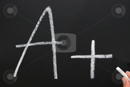 A teacher writing A+ on a blackboard. stock photo, A teacher writing A+ on a blackboard. by Stephen Rees