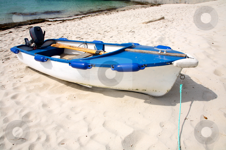 A white motorboat pulled up on the beach. stock photo, A white motorboat pulled up on the beach. by Stephen Rees