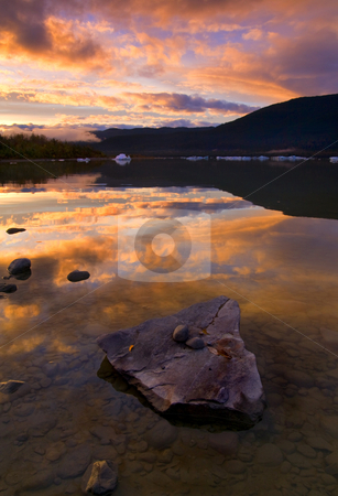 Fire and Ice stock photo, A fiery sunset sky over the still waters of Mendenhall Lake with icebergs claved off the Mendenhall Glacier dotting the lakes still waters. by Mike Dawson