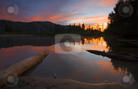 Burning Dawn stock photo, A red dawn over the still waters of Bench LAke in MT. Rainier National PArk as the cold mist hugg the still waters of the lake. by Mike Dawson
