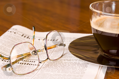 Coffee newspaper and reading glasses  stock photo, Freshly brewed coffee on a newspaper with reading glasses on wooden desk by Magdalena Ascough