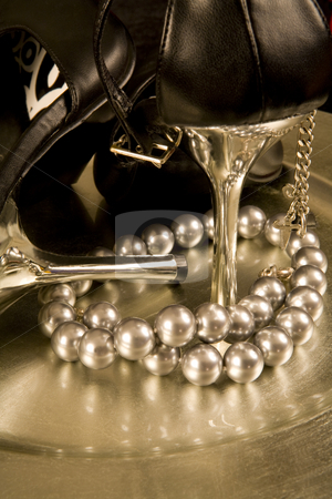 Stilettos and a string of pearls on a tray stock photo, Closeup of black stilettos with silver heels and a string of pearls on a silver tray by Magdalena Ascough