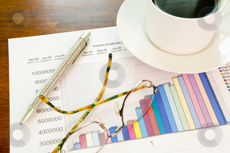 Financial graph with a pen, coffee and spectacles stock photo, A financial graph with a silver pen, spectacles and fresh black coffee by Magdalena Ascough