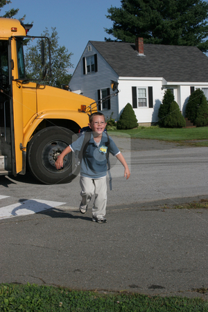 Boy and bus stock photo, Young boy running off the school bus after his first day of school. by Sue and Shawn Roberts