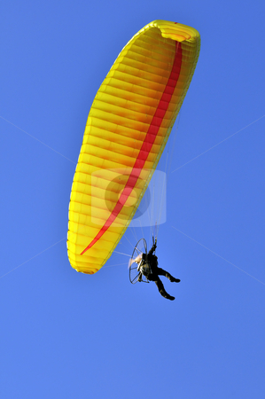 Paragliding stock photo, Man with a yellow paraglider flying in the sky by Massimiliano Leban