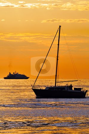 Boats at sunset stock photo, Two different kind of boats at sunset: a big yacht and a small sailboat by Massimiliano Leban