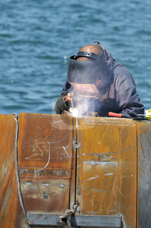 Welder stock photo, Worker welding two big pipes in a harbour by Massimiliano Leban