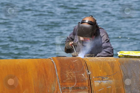 Man welding stock photo, Worker welding two big pipes in a harbour by Massimiliano Leban