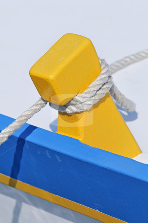Moored boat stock photo, Close-up of a yellow and blue boat moored to dock by Massimiliano Leban