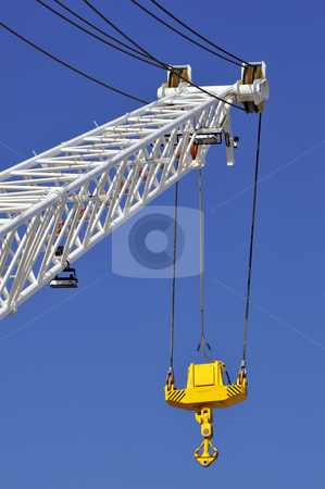 Crane stock photo, Crane arm with yellow hook agaist a blue sky by Massimiliano Leban