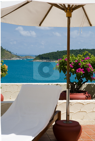 Umbrella and deck chair on patio stock photo, White umbrella and deck chair on patio with sea view by Magdalena Ascough