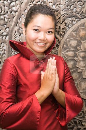 Thai woman in silk dress greeting stock photo, Young Thai woman in red silk dress greeting by Magdalena Ascough