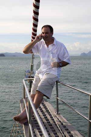 Man on yacht with mobile phone and wine stock photo, Handsome man on deck of yacht with mobile phone and drinking wine by Magdalena Ascough