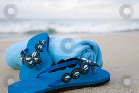 Flip flops and towel on a beach stock photo, Turquoise flip flops and towel on a beach by Magdalena Ascough