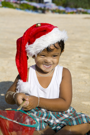 Boy with Christmas hat on beach stock photo, Little Thai boy playing and with Christmas hat on a beach by Magdalena Ascough