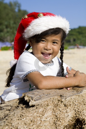 Thai girl with Christmas hat on beach stock photo, Little Thai girl with Christmas hat on a beach by Magdalena Ascough
