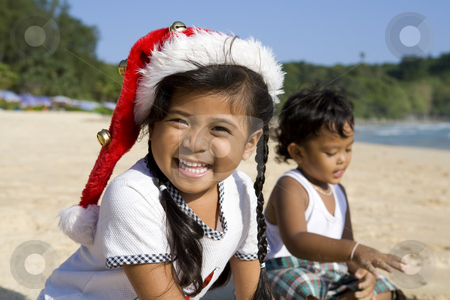 Girl with Christmas hat and boy playing on beach stock photo, Thai girl wearing a Christmas hat with a boy playing on a beach by Magdalena Ascough