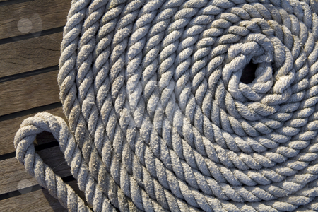 White rope on a wooden surface stock photo, White rope rolled up in a circle on a wooden surface by Magdalena Ascough
