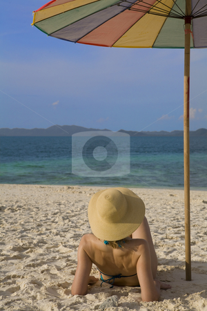 Woman on beach under a umbrella stock photo, Woman  with sunhat on a beach lying under a colorful umbrella by Magdalena Ascough